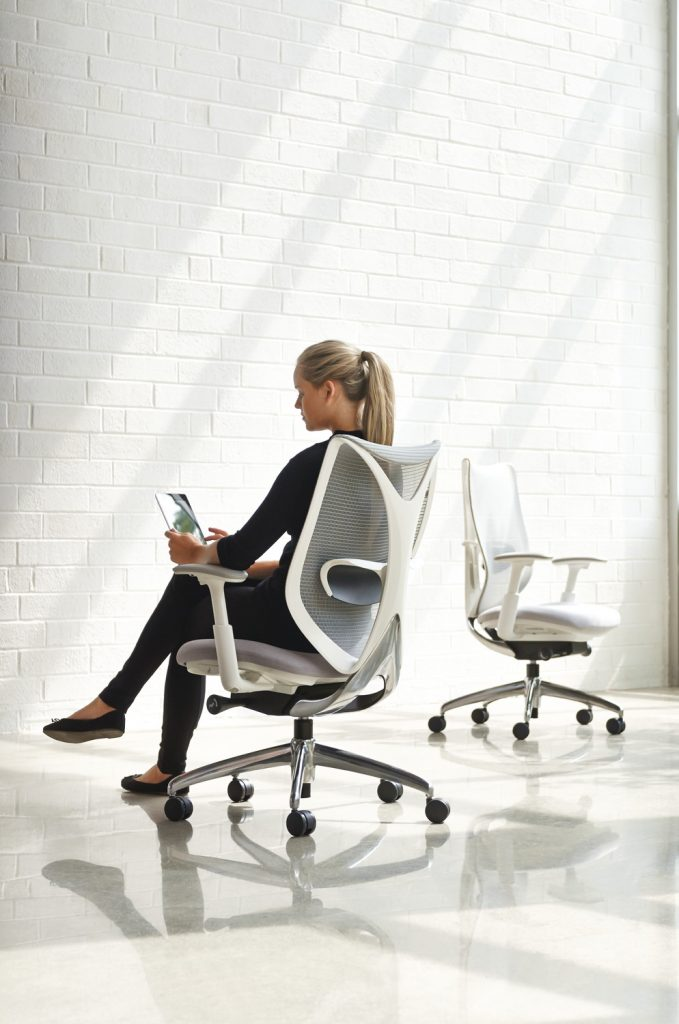 A woman sitting in a high-quality task chair that is comfortable and beautifully designed.