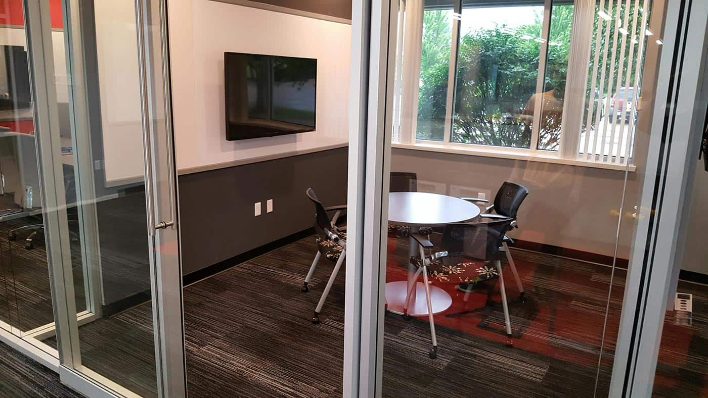 Small meeting room with sliding glass wall for audible privacy