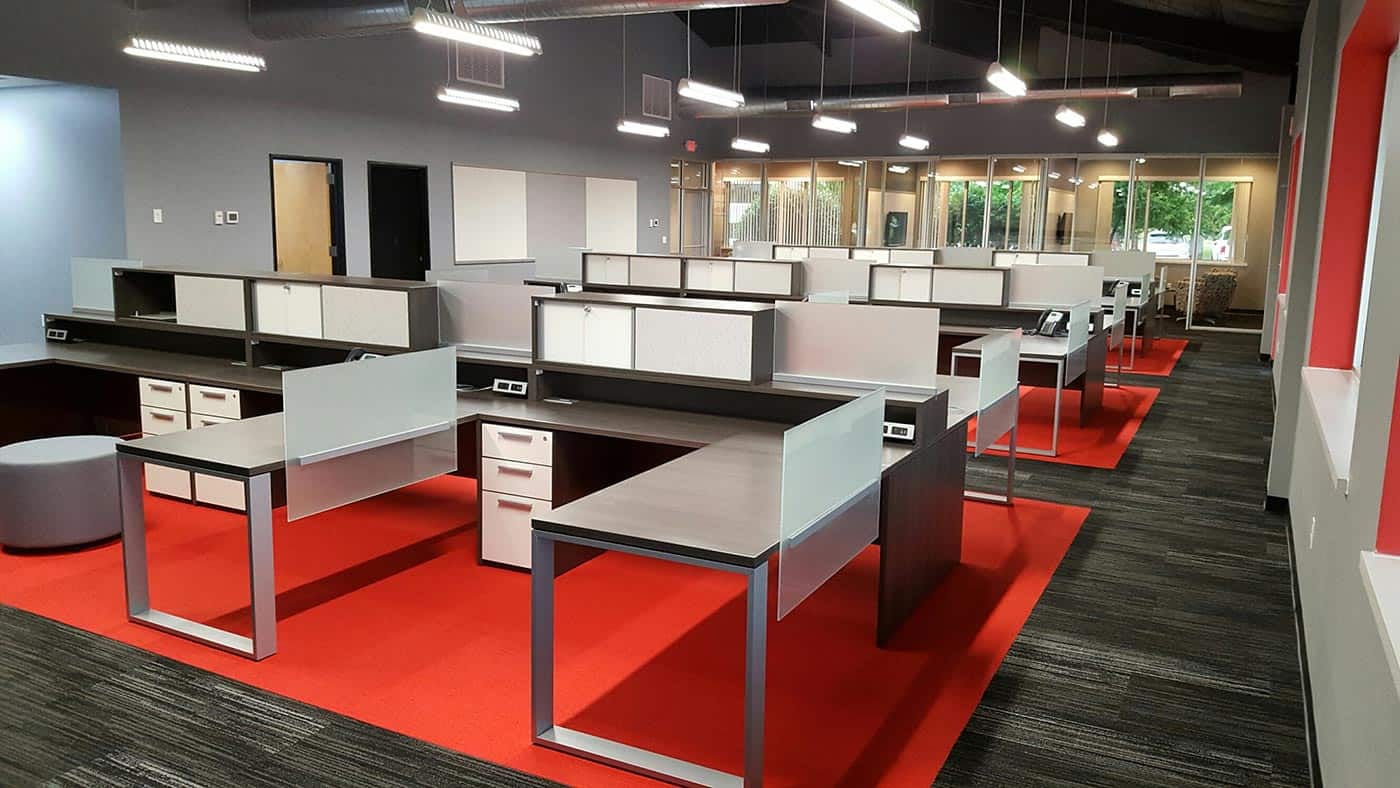 Modern open office desk layout, silver, red, dark wood colors. Sleek, minimal design and layout.