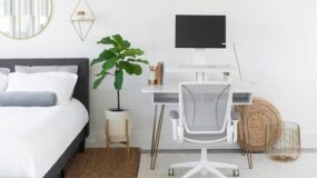 Small white desk next to bed in home