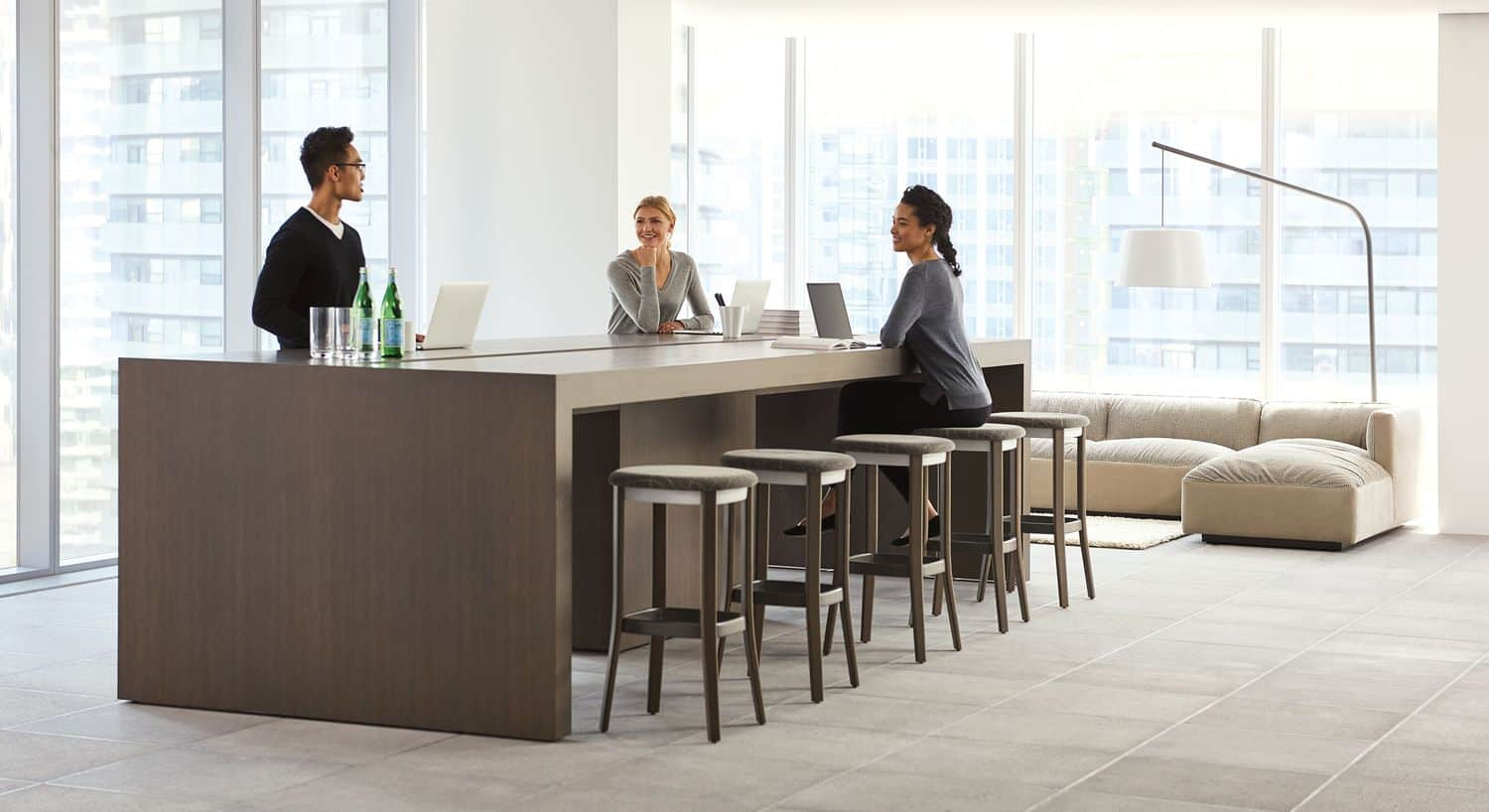 Three people standing/sitting at low community/conference table with bar stool style chairs in office